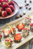 Verse die aardbeien met donkere chocolade en noten worden behandeld Royalty-vrije Stock Afbeelding