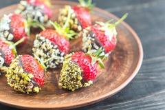 Verse die aardbeien met donkere chocolade en noten worden behandeld Stock Foto