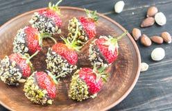 Verse die aardbeien met donkere chocolade en noten worden behandeld Stock Foto's