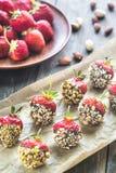 Verse die aardbeien met donkere chocolade en noten worden behandeld Royalty-vrije Stock Afbeeldingen