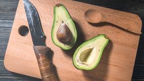 Verse die avocado in de twee helften met been op een decoratieve scherpe Raad wordt gesneden Stock Fotografie