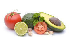 Verse die avocado door tomaat, knoflook en kalk op wit wordt omringd Stock Foto's