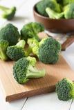 Verse die broccoli op houten lijst worden verspreid Stock Afbeeldingen