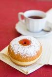Verse doughnut op een servet met een kop thee Stock Afbeeldingen