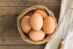 Verse eieren in oude houten mand gezet op wit servet Bereid kuiken voor Stock Foto