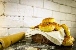 Verse eigengemaakte broodjes op mand met rustieke witte baksteenachtergrond Stock Fotografie