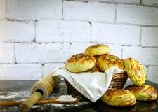 Verse eigengemaakte broodjes op mand met rustieke witte baksteenachtergrond Stock Foto