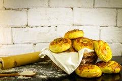 Verse eigengemaakte broodjes op mand met rustieke witte baksteenachtergrond Stock Afbeelding