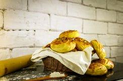 Verse eigengemaakte broodjes op mand met rustieke witte baksteenachtergrond Stock Afbeeldingen