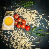 Verse eigengemaakte Italiaanse deegwaren met ingrediënten voor het smakelijke koken: parmezaanse kaas, olie, tomaten en arugula o royalty-vrije stock fotografie