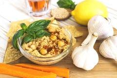 Verse eigengemaakte organische hummus met pitabroodje cheaps en basilicum Royalty-vrije Stock Foto's