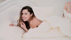 Verse en gelukkige donkerbruine vrouw die in bed thuis liggen Mooie meisjesdraaien en glimlach Vrolijke vrouw die in bed flirten Stock Foto
