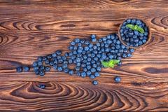 Verse en heldere bosbessen Gezonde, rijpe, ruwe en heldere donkerblauwe bessen op een houten achtergrond De ruimte van het exempl Royalty-vrije Stock Fotografie