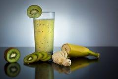 Verse en sappige banaan en kiwi smoothie in glas met vruchten rond - Hoog - kwaliteits gezond concept op zwarte en grijze achterg stock afbeeldingen