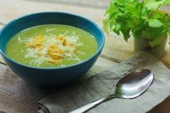 Verse fijngestampte soep met broccoli en slabonen in een blauwe plaat op een houten achtergrond stock afbeelding