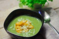 Verse fijngestampte soep met broccoli en slabonen in zwarte plaat op houten achtergrond stock afbeeldingen