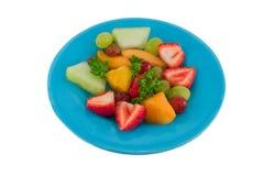 Verse fruitsalade op blauwe plaat Stock Foto