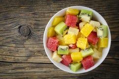 Verse fruitsalade op houten lijst Stock Afbeeldingen
