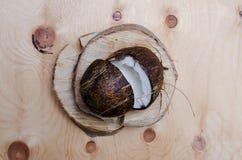 Verse gehalveerde kokosnoot op lichte houten achtergrond Organisch gezond voedselconcept Schoonheid en Kuuroord De stijl van de E Stock Afbeeldingen