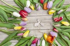 Verse gekleurde tulpen vooraan een houten achtergrond met Paashazen Stock Fotografie