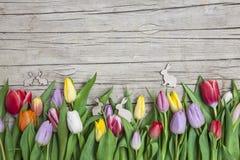 Verse gekleurde tulpen vooraan een houten achtergrond met Paashazen Stock Foto