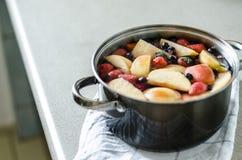 Verse gekookte appel kompot met bessen in pot op keukenhanddoek, vers fruitdrank, de drank van de poetsmiddelzomer Stock Fotografie