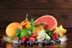 Verse gele carambola, peren, rode aardbeien, kalk, muntbladeren, grapefruit op een vage houten achtergrond Stock Afbeeldingen