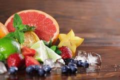 Verse gele carambola, rode aardbeien, kalk, muntbladeren, grapefruit op een vage houten achtergrond Stock Foto's