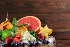 Verse gele carambola, rode aardbeien, kalk, muntbladeren, grapefruit op een vage houten achtergrond Stock Afbeeldingen