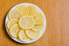 Verse gele citroenenplakken op een houten achtergrond zoete kalk, vitamine C De plak van de citroen stock fotografie