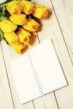 Verse gele tulpen met lege open blocnote op houten achtergrond stock foto's