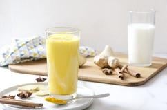 Verse gemaakte kurkuma latte met kaneel, gember en steranijsplant bij de keukenlijst Close-up van verschillende ingrediënten voor stock foto's