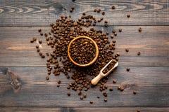 Verse geroosterde koffiebonen in kom en lepel op de donkere houten mening van de lijstbovenkant Klaar voor gebruik Stock Afbeeldingen