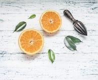 Verse gesneden sinaasappelen met bladeren en houten verbrijzeling voor fruit, rustieke houten achtergrond, hoogste mening, ruimte royalty-vrije stock afbeeldingen