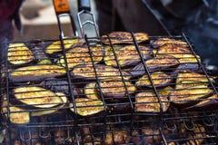 Verse gezonde aubergine of aubergine die op een barbecuegrill voorbereidingen treffen over houtskool De geroosterde plakken van a Stock Afbeeldingen