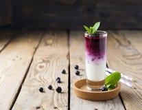 Verse gezonde bosbes smoothies in een glas met bessen en muntbladeren op een houten tribune Royalty-vrije Stock Afbeeldingen