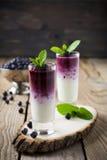 Verse gezonde bosbes smoothies in een glas met bessen en muntbladeren op een houten tribune Royalty-vrije Stock Foto's
