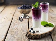 Verse gezonde bosbes smoothies in een glas met bessen en muntbladeren op een houten tribune Stock Foto's