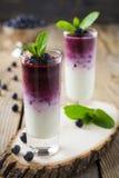 Verse gezonde bosbes smoothies in een glas met bessen en muntbladeren op een houten tribune Stock Foto