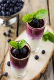 Verse gezonde bosbes smoothies in een glas met bessen en muntbladeren op een houten tribune Stock Afbeeldingen
