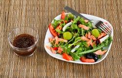 Verse gezonde salade en het kleden zich op natuurlijk bamboeonderleggertje Royalty-vrije Stock Foto's