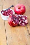 Verse granaatappelfruit en pitten in witte kom stock afbeeldingen