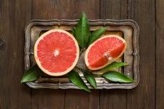 Verse grapefruit met bladeren op een dienblad stock foto's