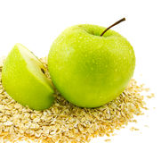 Verse groene appel met een segment op havervlokken. Stock Afbeeldingen