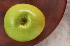 Verse groene appel op rustieke ceramische schotel Stock Afbeeldingen