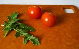 Verse groene arugulabladeren en kersentomaten op houtvezelplaat royalty-vrije stock fotografie