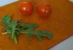 Verse groene arugulabladeren en kersentomaten op houtvezelplaat stock foto's