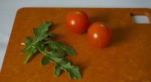 Verse groene arugulabladeren en kersentomaten op houtvezelplaat royalty-vrije stock afbeelding