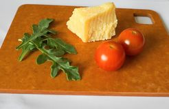 Verse groene arugulabladeren, kersentomaten en parmezaanse kaaskaas op houtvezelplaat royalty-vrije stock foto's