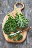 Verse groene boerenkoolbladeren op een scherpe raad op een houten lijst Royalty-vrije Stock Fotografie